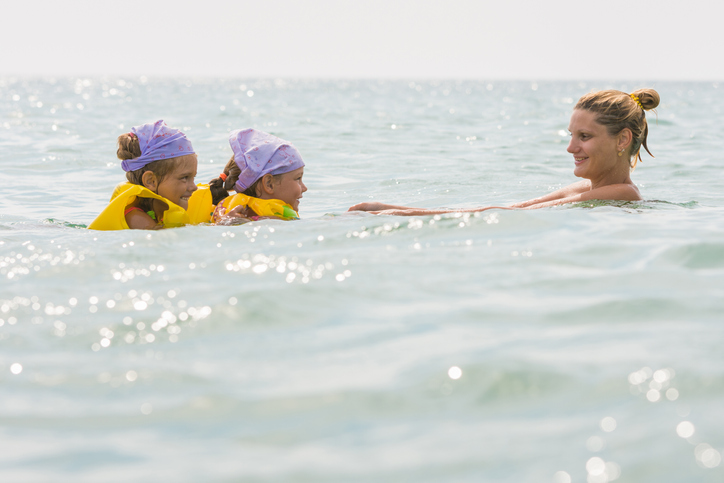 mother swimming within arms length of two daughters floating in sea with vests on