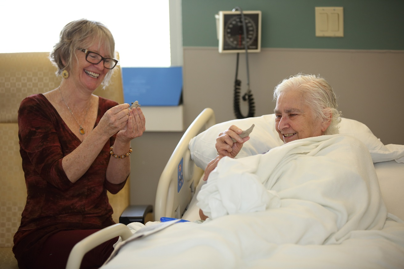 elderly hospital patient smiling while making music with artist volunteer