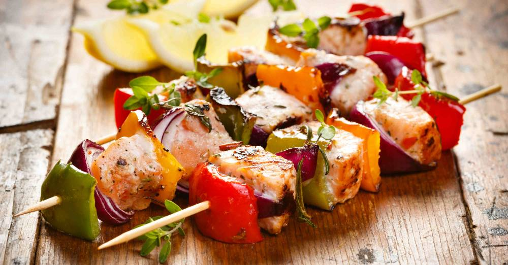 Salmon and vegetable kebabs on a wooden plank table.
