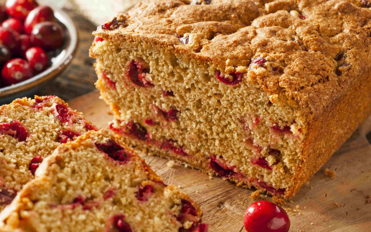 Closeup image of a loaf of cranberry flax pumpkin bread sliced on a wooden cutting board.