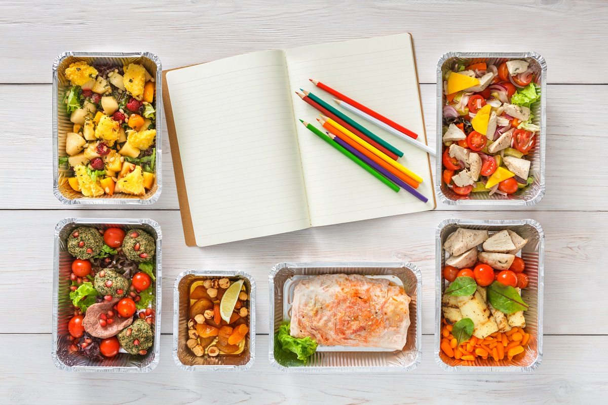top-down view of notepad and colored pencils for meal plan surrounded by healthy portioned meals