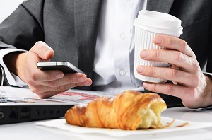 closeup of man's hands multitasking with disposable coffee cup, cellphone, breakfast sandwich and laptop