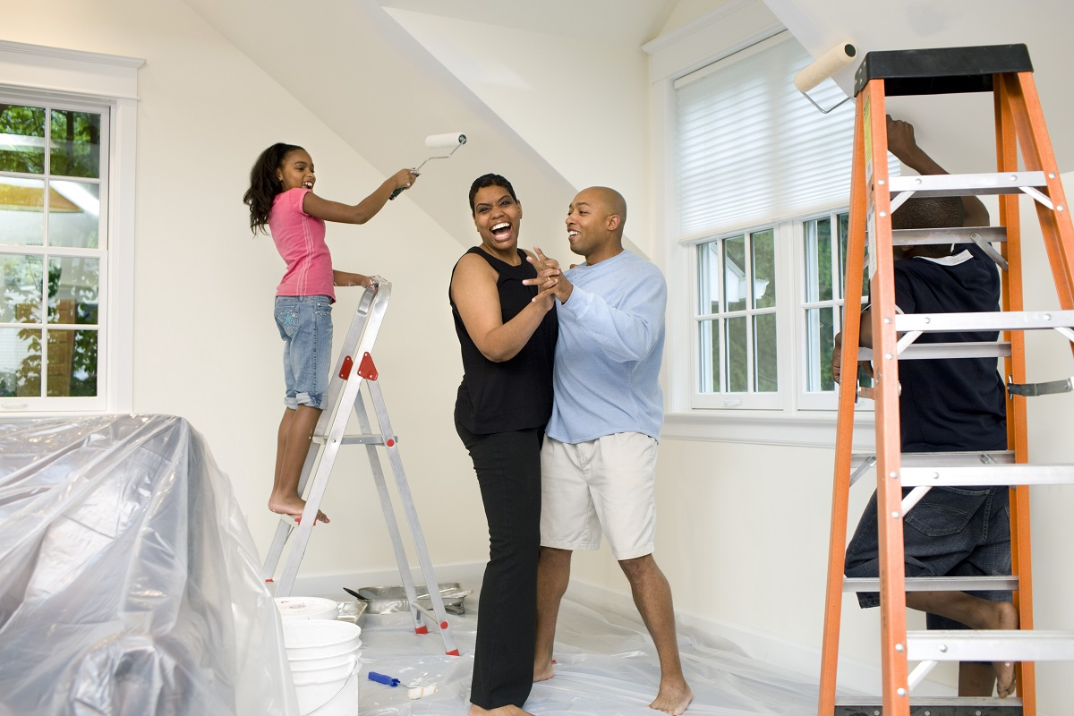 young family painting a bedroom with parents dancing and daughter smiling