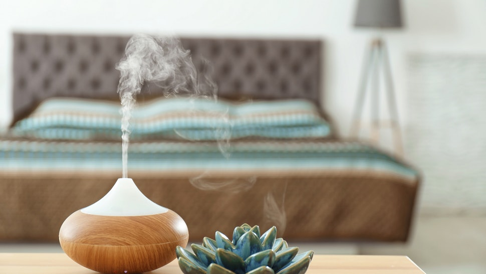 small humidifier in foreground with bedroom furniture in background