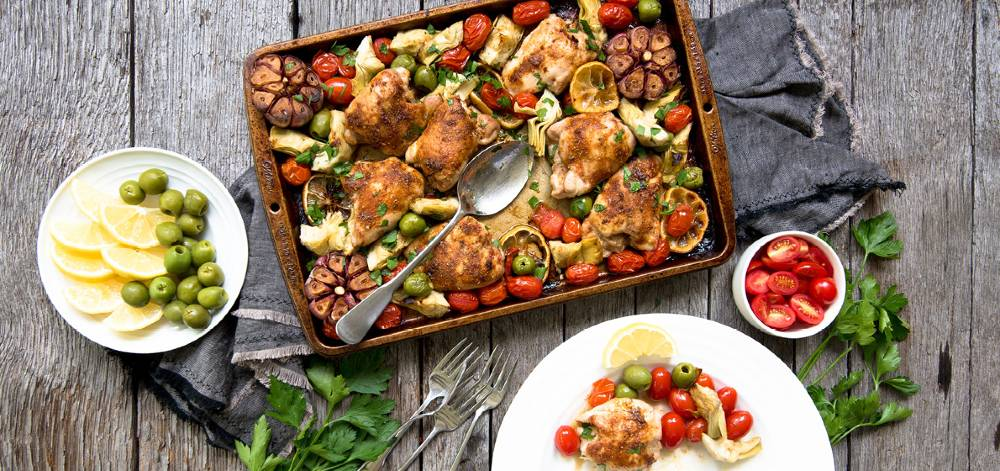 Overhead view of a pan of roasted chicken with olives, artichokes, grape tomatoes, fresh herbs and lemon slices.