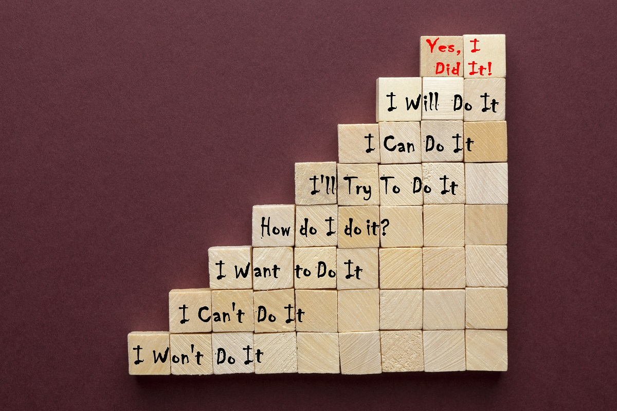 wooden blocks arranged as steps with increasingly positive motivational quotes on each level