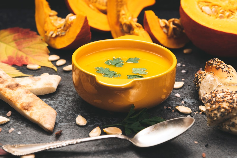 A copper bowl of pumpkin butternut squash bisque, sprinkled with herbs, on a black slate surface, surrounded by slices of pumpkin and pumpkin seeds, with a spoon beside/