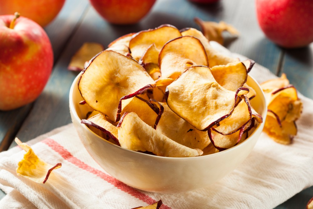 Bowl full of baked apple chips set on a stack of cloth napkins, with apples surrounding it.