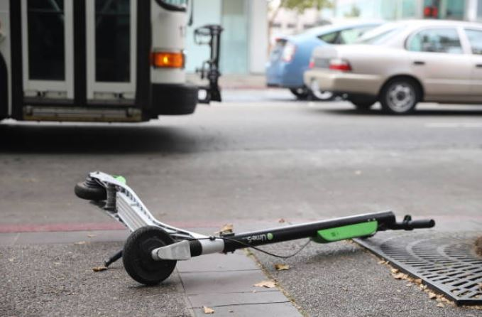 electric scooter lying abandoned on its side in the street in front of a city bus