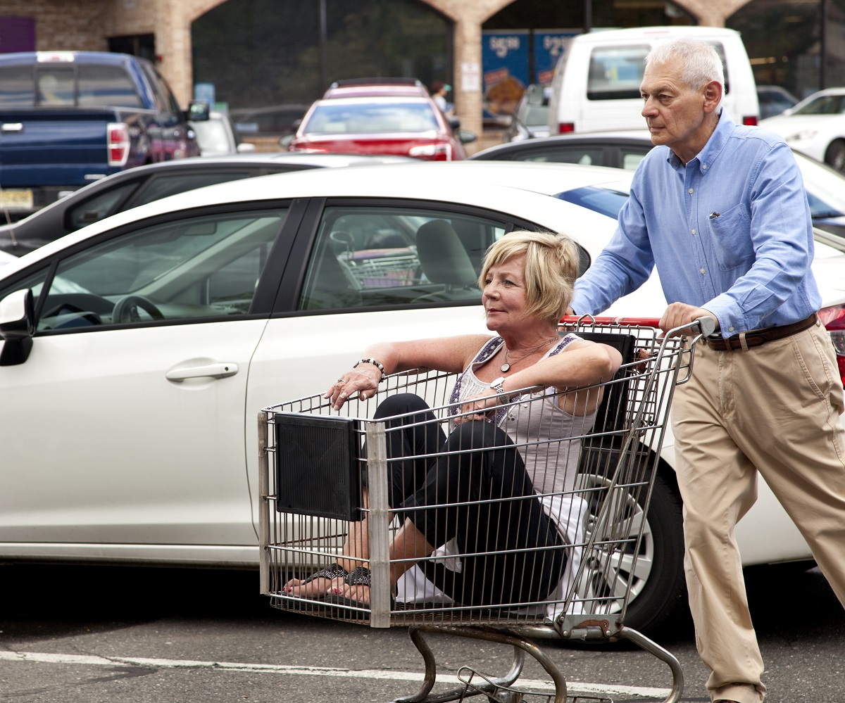 older couple in grocery parking lot with woman in buggy and man pushing