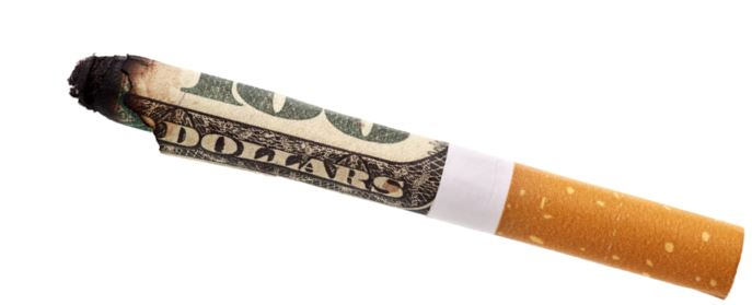 lit cigarette wrapped by hundred dollar bill indicating burning money