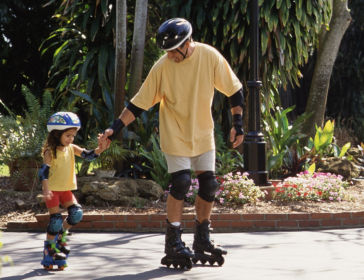 father and daughter on inline skates both wearing appropriate protective gear
