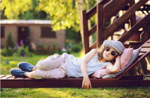 young girl in casual summer clothes relaxing in backyard indicating staycation