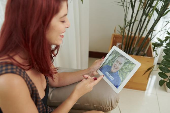 woman on couch holding tablet showing skype call with her father