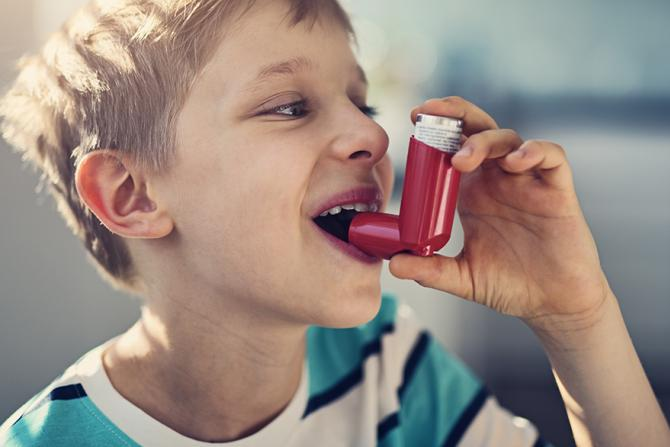 child with asthma using a rescue inhaler
