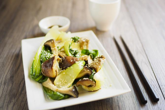 garlic ginger mushrooms and bok choy stir fry on white plate with chopsticks