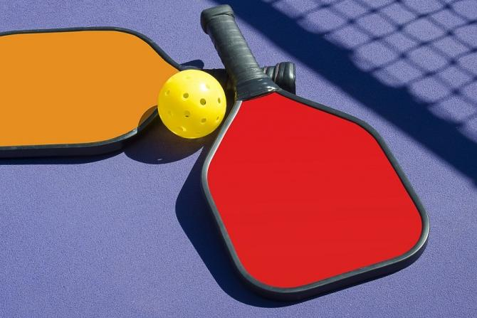 orange and red pickleball paddles on the foreground in front of the shadow of a net