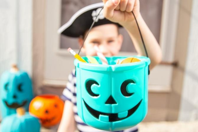 boy in pirate costume holding teal pumpkin filled with hypoallergenic treats