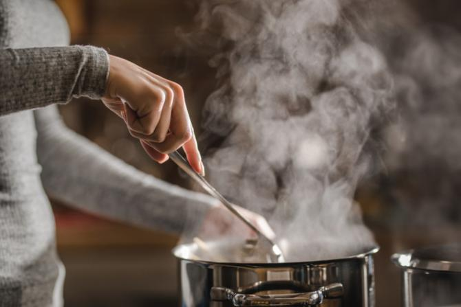 A woman's hand stirs a spoon in a steaming stainless steel stockpot.
