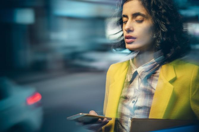 young business woman dizzy with eyes closed while holding phone