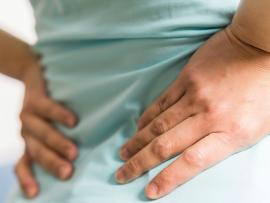 closeup of woman's hands clasping her lower back as though it's in pain
