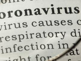 dictionary showing definition of coronavirus through magnifying glass