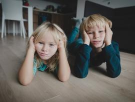 A brother and sister lying on the floor with their heads in their hands and bored facial expressions..