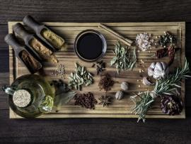 A variety of fresh herbs and spices arranged on a wooden cutting board.