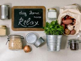 """Jarred grains, canned food, a bag of potatoes and a potted parsley plant surround a chalkboard that reads: """"Stay Home and Relax.""""."""""""