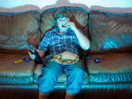 overweight teenager sitting on the couch eating junk food and watching TV