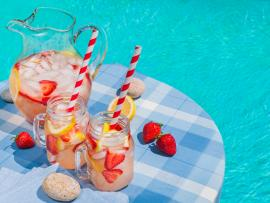 A pitcher and mason jars filled with homemade pink lemonade, on a table beside an outdoor pool.