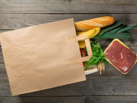 Paper bag with healthy groceries spilling out.