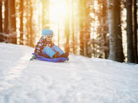 little boy sledding down a snowy hill wearing a helmet