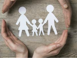 two hands surrounding a paper cut out of a family
