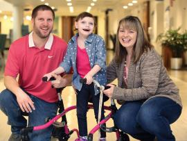 smiling child with scoliosis using walker supported by happy parents