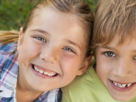 two young children hugging with their heads together