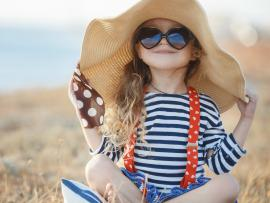 Young girl wearing sunglasses and large sun hat in field