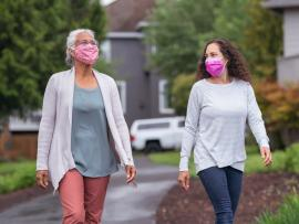 two women walking outside for exercise while wearing masks to protect against coronavirus