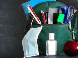 backpack on desk with hand sanitizer, mask, school supplies