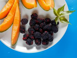 fresh blackberries and cantaloupe on a plate with a sprig of mint