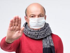 bald man with medical mask on and hand out as if to say stop