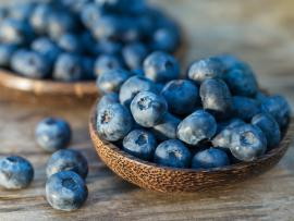 ripe blueberries in a wooden bowl