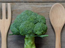 fresh broccoli on cutting board next to a knife and a spoon