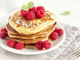 plate of corn pancakes with fresh raspberries on top