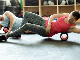 man and woman foam rolling at the gym