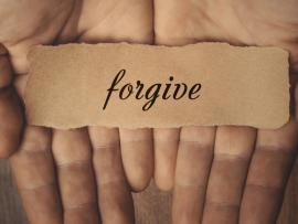 forgive written on a piece of paper and resting in palm of hand