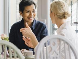 Two female friends talking over a cup of coffee.