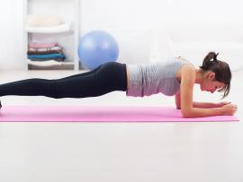 woman doing a plank exercise on a yoga mat