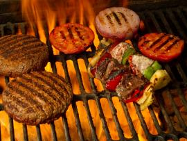 burgers, vegetable skewers, and roasting tomatoes and onions over a charcoal fire