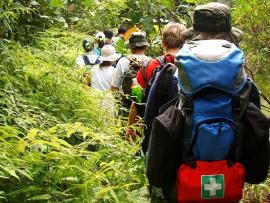 children hiking with first aid kit on backpack